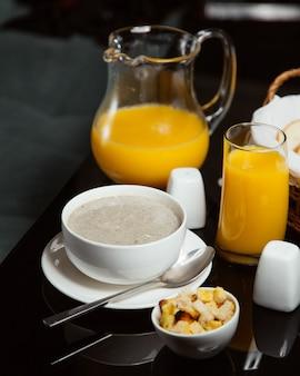 Sopa de cogumelos com suco de laranja e biscoitos.