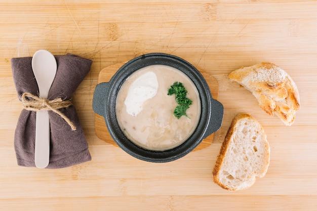 Sopa de cogumelos deliciosa com fatias de pão; guardanapo e colher na mesa de madeira