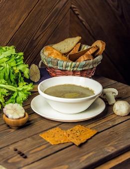 Sopa de cogumelos saborosa com fatias de pão fino.
