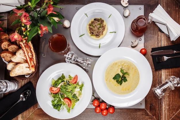Sopa de cogumelos, salada e purê de batatas em uma mesa de madeira
