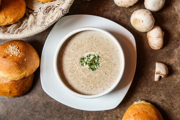 Sopa de cogumelos vista superior com um pedaço de pão na mesa