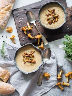 Sopa de creme da prima em umas bacias e no baguette azuis na placa rústica da tabela e da madeira. conceito de comida de outono. vista do topo
