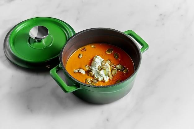 Sopa de creme de abóbora apetitosa e saudável em uma tigela verde sobre uma superfície de mármore