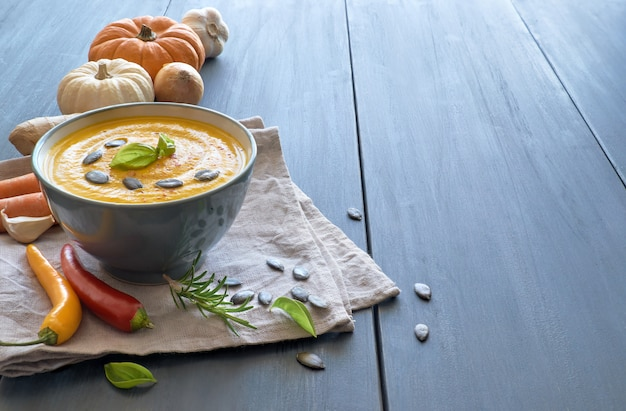 Sopa de creme de abóbora, cenoura e gengibre em tigela de cerâmica