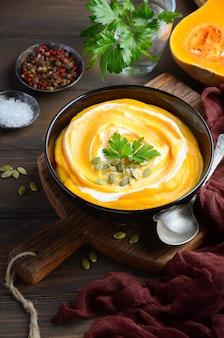 Sopa de creme de abóbora com creme e sementes de abóbora na mesa de madeira.