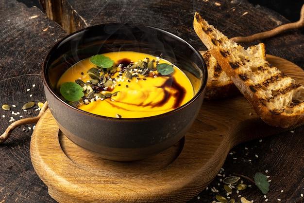 Sopa de creme de abóbora com pão branco grelhado. semente de abóbora, balsâmico, quinua frita.