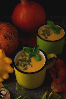 Sopa de creme de abóbora com sementes de abóbora em uma caneca