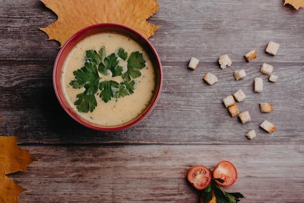 Sopa de creme de abóbora vegetal vegetariano com salsa em uma tigela sobre uma mesa de madeira com tomates e biscoitos.