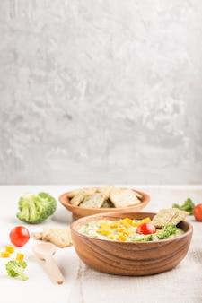 Sopa de creme de brócolis verde com biscoitos e queijo em uma tigela de madeira em uma parede branca e cinza. vista lateral, copyspace.