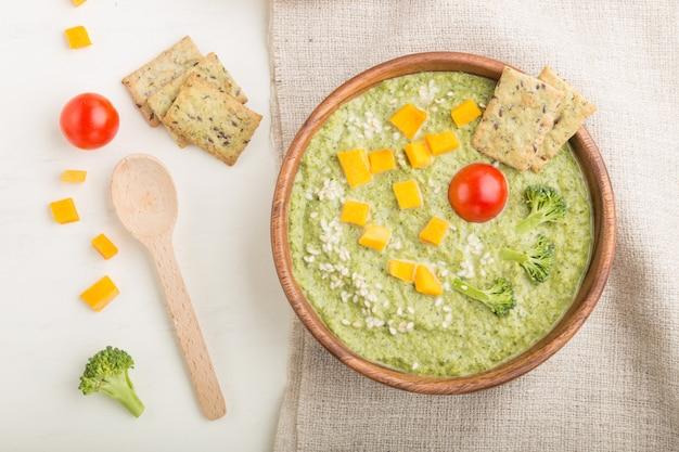 Sopa de creme de brócolis verde com biscoitos e queijo em uma tigela de madeira. vista do topo.