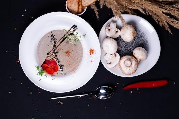 Sopa de creme de cogumelos com croutons em uma superfície escura. vista do topo