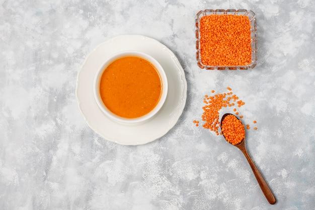 Sopa de creme de lentilha vermelha na luz em uma tigela branca, vista superior