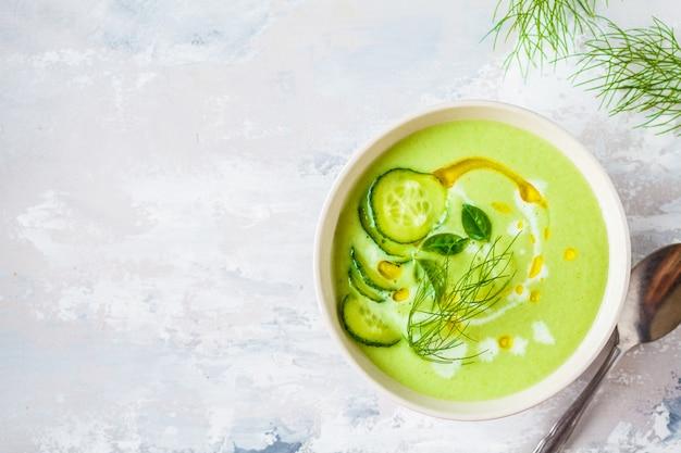 Sopa de creme de pepino frio vegan em tigela branca sobre um cinza