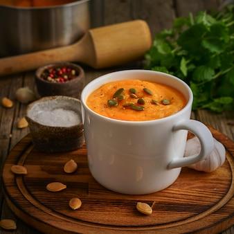 Sopa de creme de pupmkin no copo na tabela de madeira marrom, vista lateral. purê dietético vegetariano
