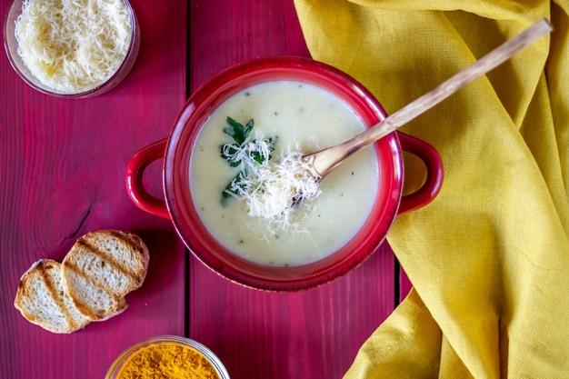 Sopa de creme de queijo em madeira vermelha