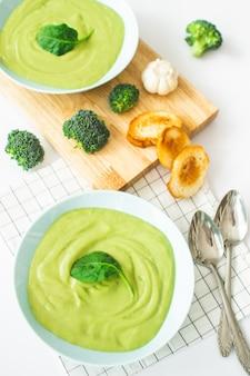 Sopa de creme dos brócolis na placa azul pastel no fundo branco. comida saudável