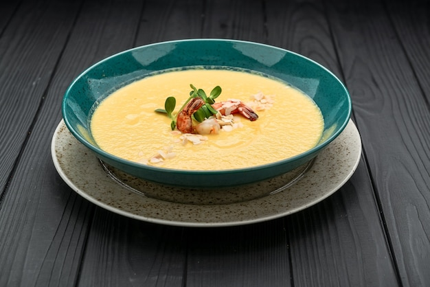 Sopa de creme fresco com camarão e vegetais na superfície preta