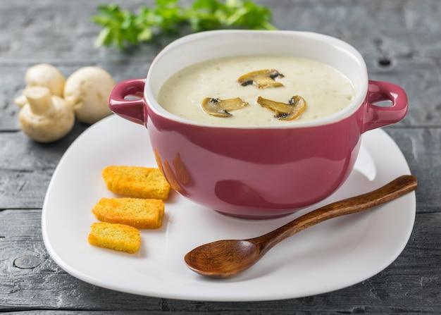 Sopa de creme preparada na hora, de cogumelos com croutons em um prato branco com uma colher de pau escura