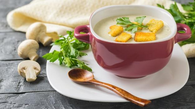 Sopa de creme preparada na hora de cogumelos com croutons em um prato branco com uma colher de pau