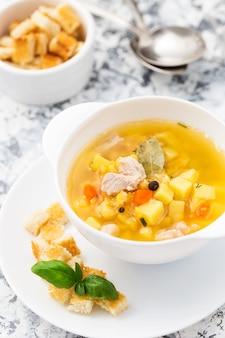 Sopa de ervilha amarela com carne de frango em uma tigela branca e torradas