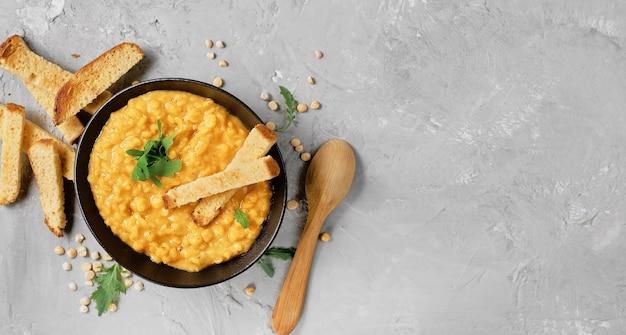 Sopa de ervilha com legumes e temperos em uma tigela de barro, ao lado de uma colher de pau. vista superior da sopa de ervilha amarela quente, com foco na parte superior do prato. layout em mesa cinza de concreto com espaço de cópia