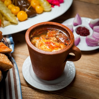 Sopa de ervilha deliciosa com carne em um copo potty em uma mesa de madeira. vista de alto ângulo.