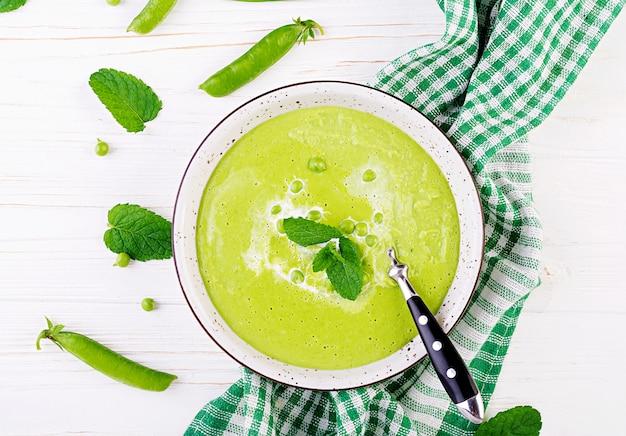 Sopa de ervilha verde em tigela na mesa de madeira