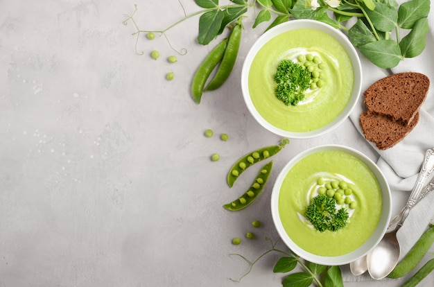 Sopa de ervilha verde em umas bacias no fundo concreto ou de pedra cinzento, vista superior, configuração lisa.