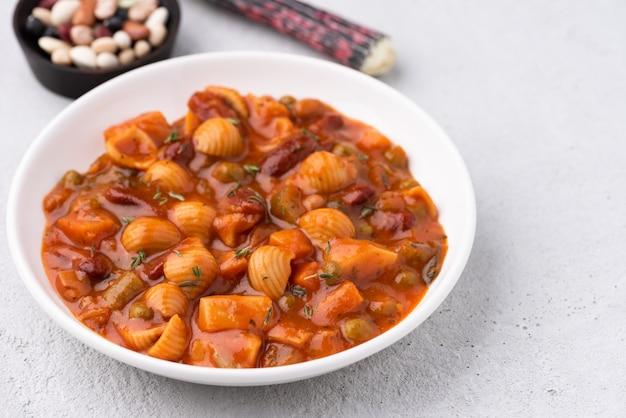 Sopa de ervilhas de grãos de macarrão vegetal em molho de tomate