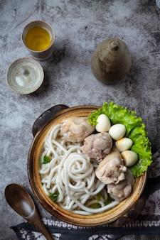 Sopa de estilo asiático com macarrão, carne de porco e cebolinha estreitamente em uma tigela em cima da mesa.