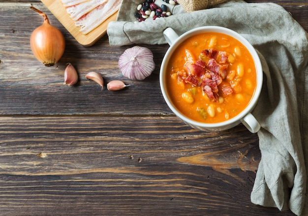 Sopa de feijão caseiro em uma tigela branca sobre fundo de madeira rústico com ingredientes. vista do topo.