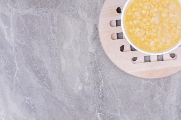 Sopa de feijão de ervilha em uma tigela de cerâmica branca no mármore