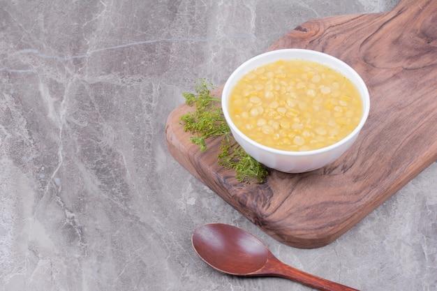 Sopa de feijão de ervilha em uma travessa de madeira com ervas ao redor.