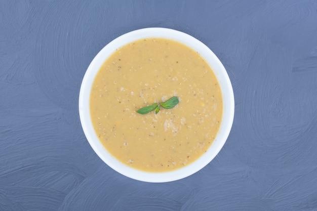 Sopa de feijão de lentilha verde em um prato branco.