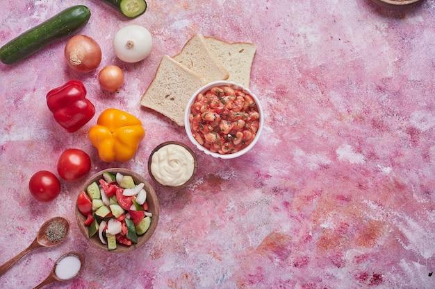 Sopa de feijão em molho de tomate com salada de legumes.