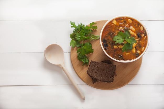 Sopa de feijão em panela de barro com tomate, azeitonas e salsa, colher de pau na mesa de madeira branca.