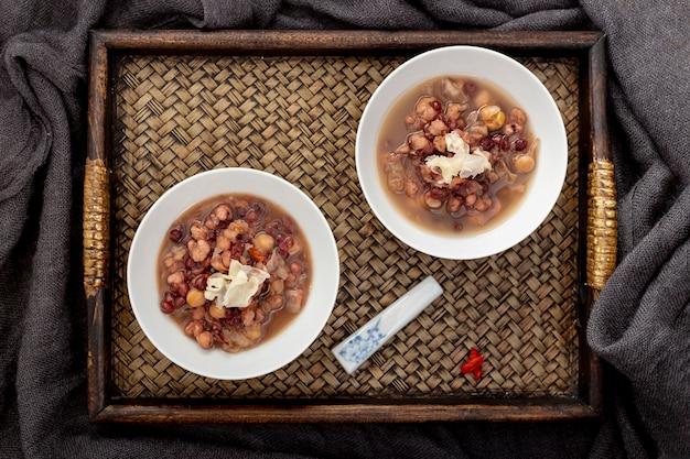 Sopa de feijão em uma jarra em uma bandeja de madeira