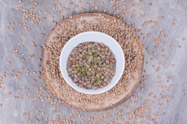 Sopa de feijão verde lentilha em caldo em um prato branco.