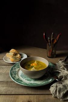 Sopa de frango caseiro, pão e talheres em um copo