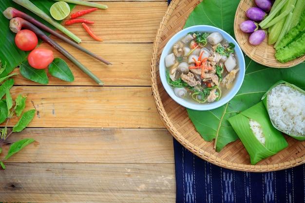 Sopa de frango picante estilo do norte e material alimentar em fundo de madeira