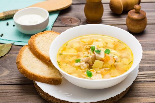 Sopa de frango pronto-a-comer com batatas e ervas em uma tigela branca sobre uma mesa de madeira