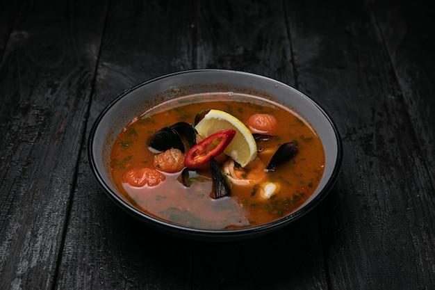 Sopa de frutos do mar com frutos do mar e molhos em mesa de madeira escura