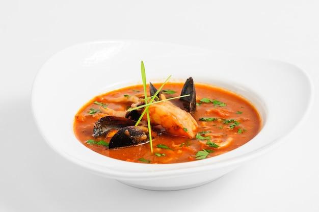 Sopa de frutos do mar em prato branco