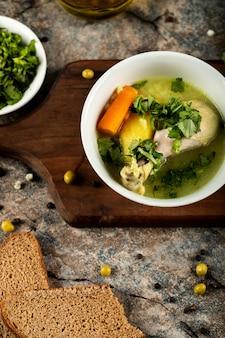 Sopa de galinha com ervas e salada verde, em uma tigela branca