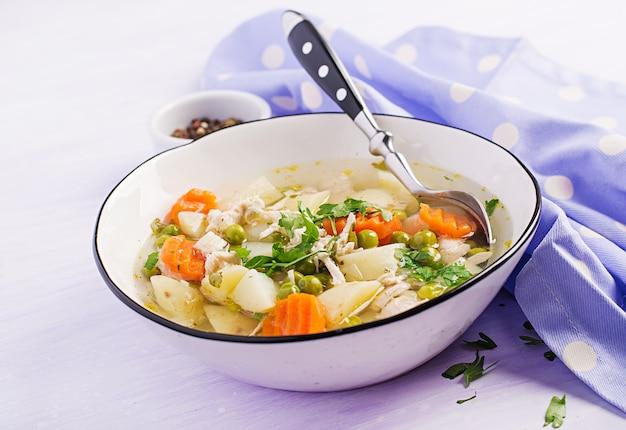 Sopa de galinha com ervilhas, cenouras e batatas em uma tigela branca em uma luz.