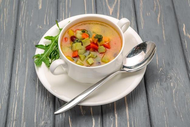 Sopa de galinha com legumes. em uma mesa de madeira