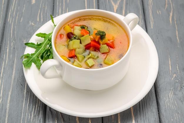 Sopa de galinha com legumes. na mesa de madeira
