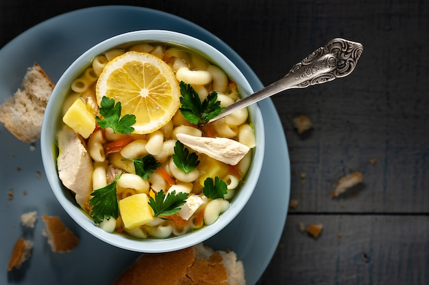 Sopa de galinha com macarrão e uma fatia de limão