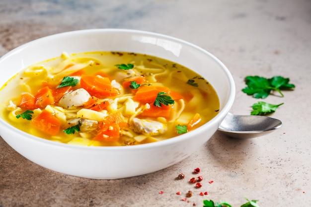 Sopa de galinha com macarrão, salsa e legumes em um prato branco.