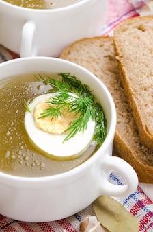 Sopa de galinha com ovo e endro em um copo